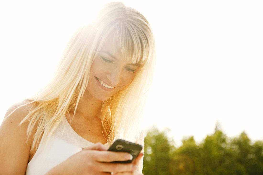 Junge Frau mit Handy im Gegenlicht