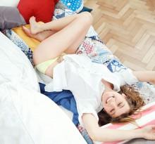 junge Frau verspielt und lachend auf Sofa