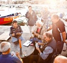 alte Fischer spielen Karten im Hafen