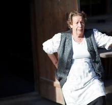 Bauersfrau vor Hütte