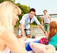 Vier Freunde beim Bootfahren am Fluss