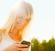 Junge Frau schreibt am Handy in der Sonne