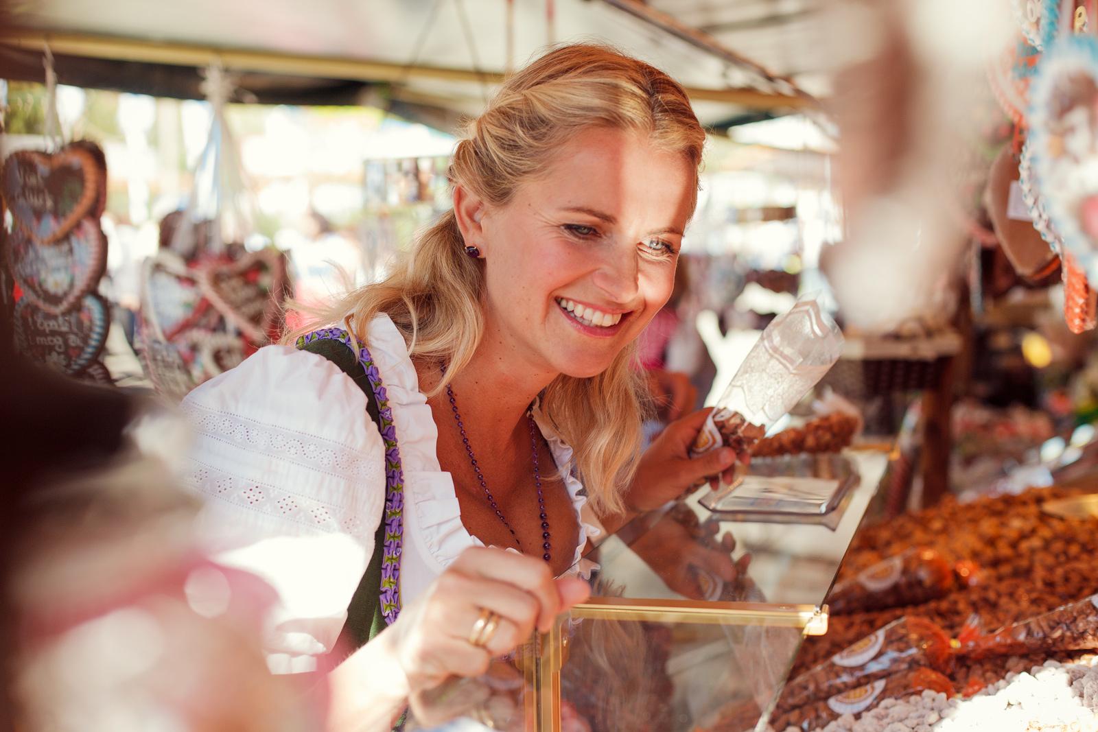 Frau im Dirndl am Süßigkeitenstand