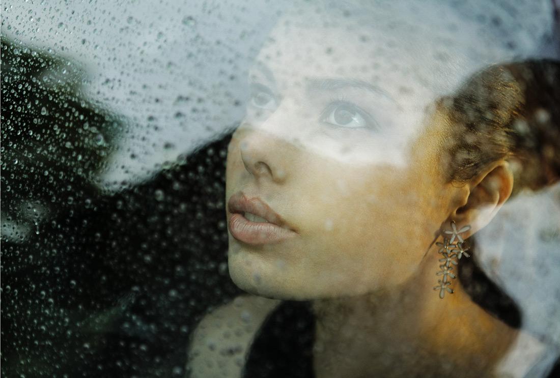 Junge Frau hinter verregnetem Fenster