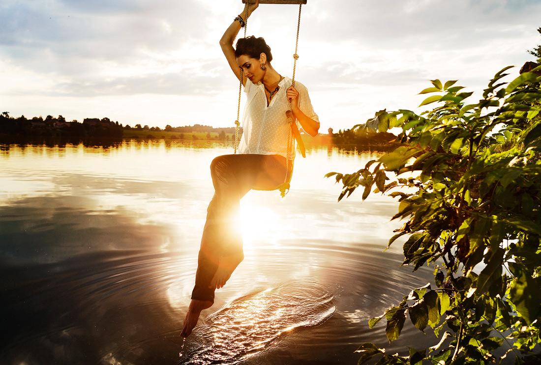 Frau auf Schaukel bei Sonnenuntergang am See