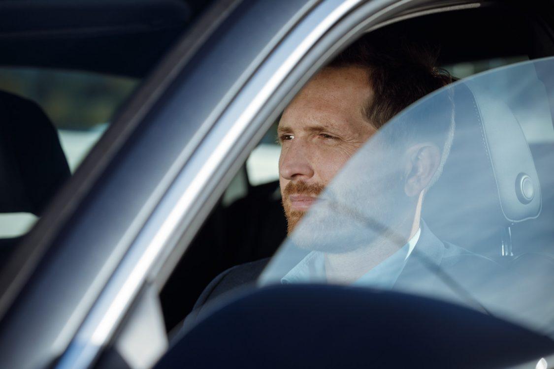 Mann im Auto mit Reflexionen in der Scheibe