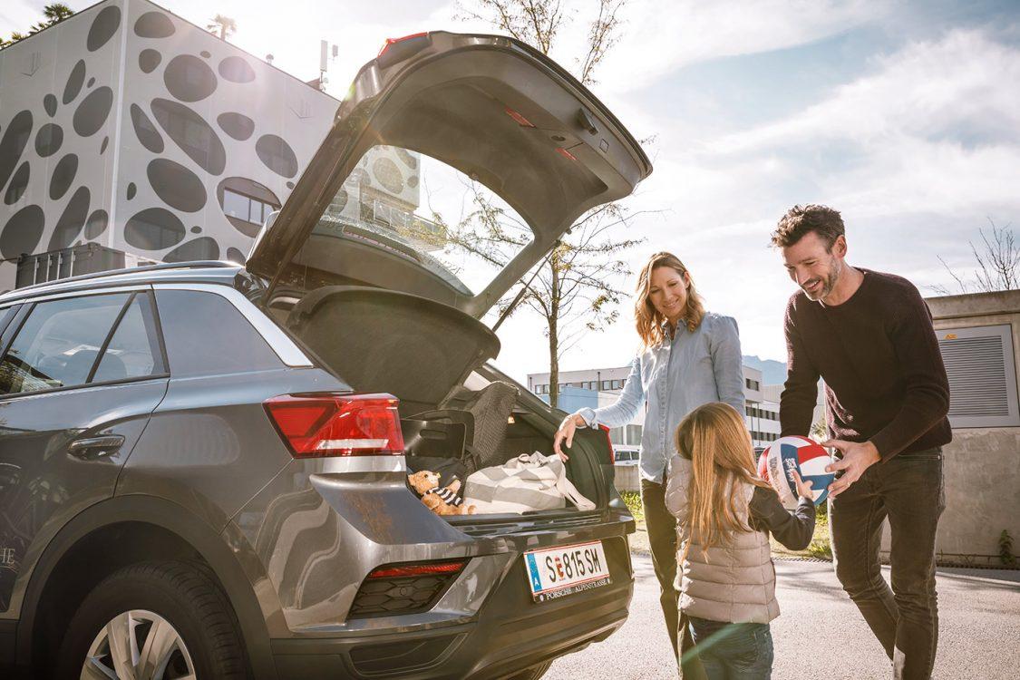 Familie mit Kind beladet Auto