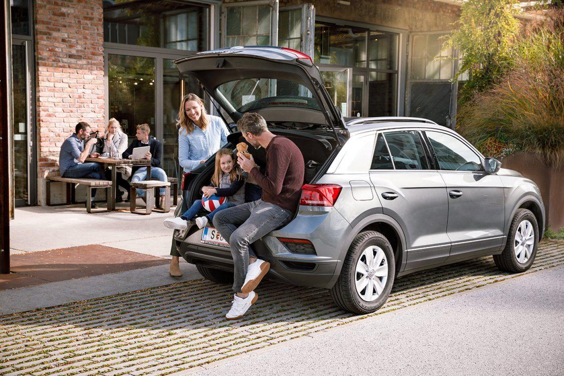 junge Familie sitzt am Auto