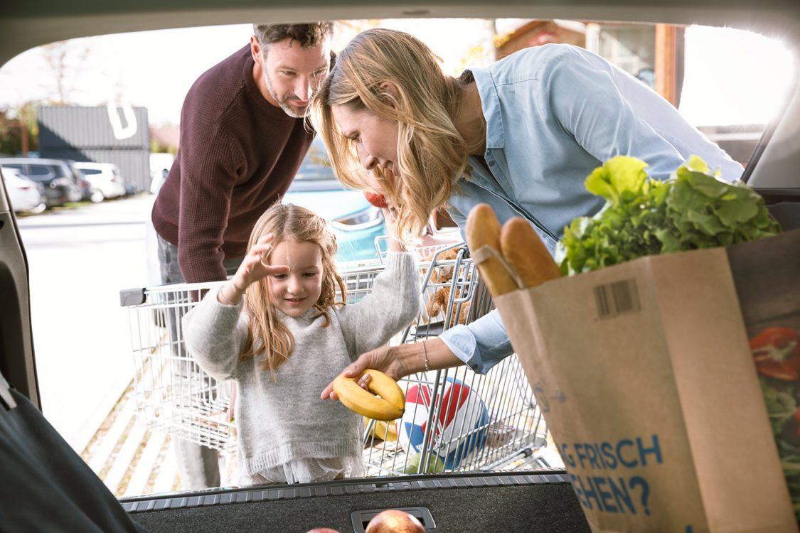 Familie belädt Kofferraum nach Einkauf