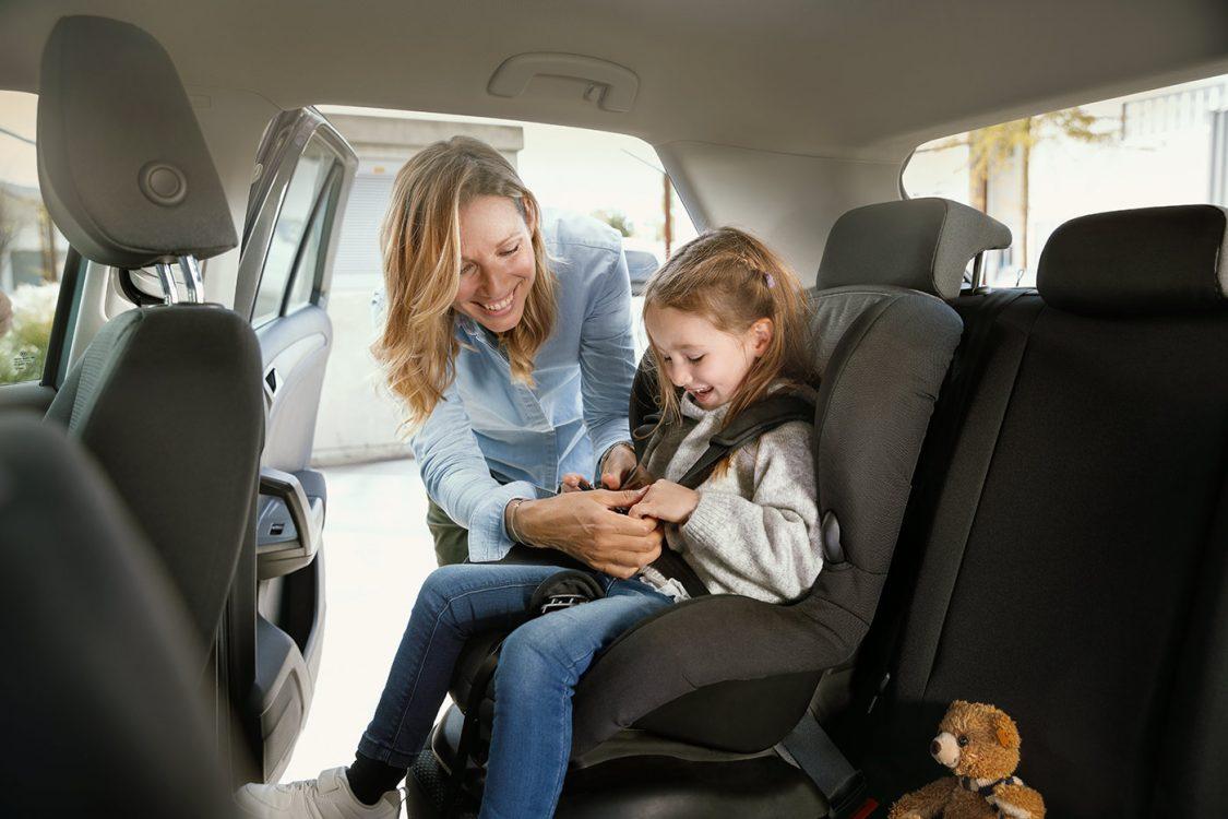 Junge Mutter bringt Kind ins Auto