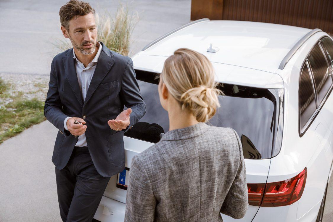 Paar diskutiert am Auto lehnend